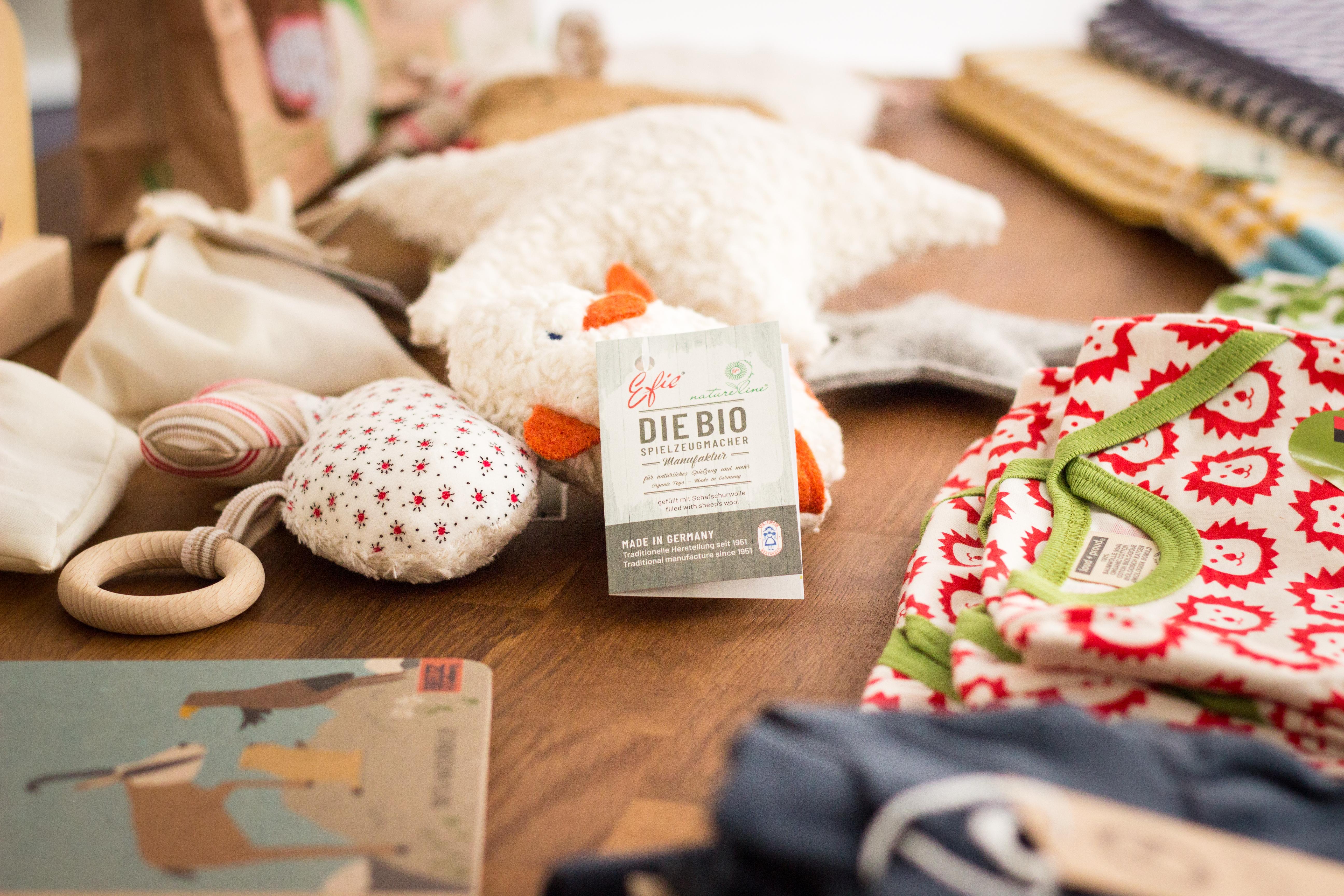 Kleinkindspielzeug, Bücher, Decken und Oberteile auf einem Tisch